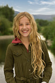 Portrait of smiling girl outdoors with view of mountains and water