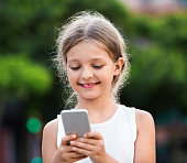 Portrait of smiling cheerful glad girl playing with mobile phone outdoors