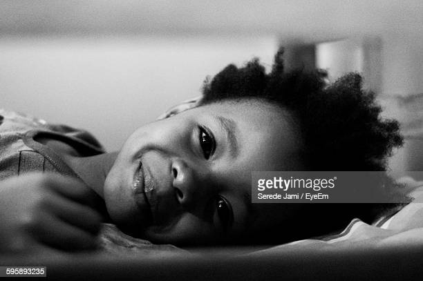 Portrait Of Smiling Girl Relaxing On Bed At Home