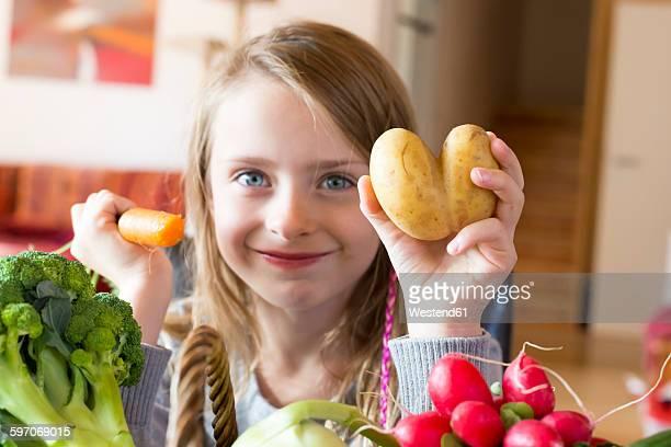 Portrait of smiling girl showing fresh vegetables