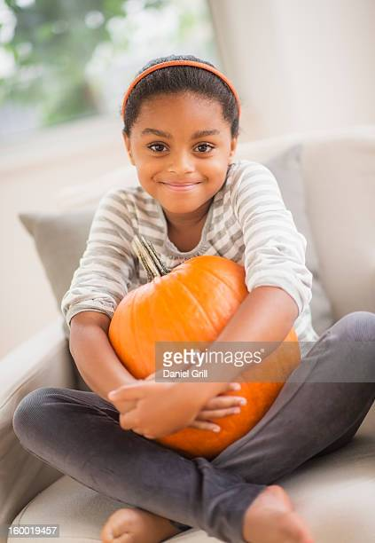 Portrait of smiling girl (6-7) sitting on sofa with pumpkin