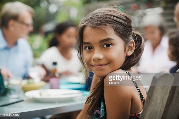 Portrait of smiling girl sitting with family at outdoor dining table