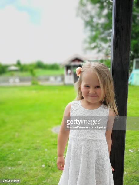 Portrait Of Smiling Girl Standing Against Pole On Grassy Field