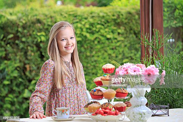 Portrait of smiling girl standing behind laid table