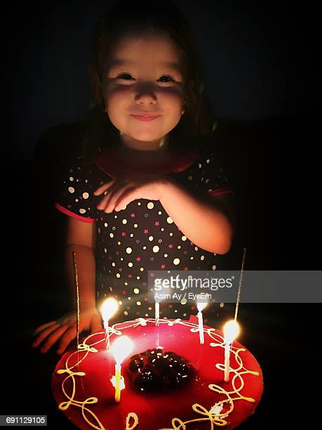 Portrait Of Smiling Girl Standing By Birthday Cake In Darkroom