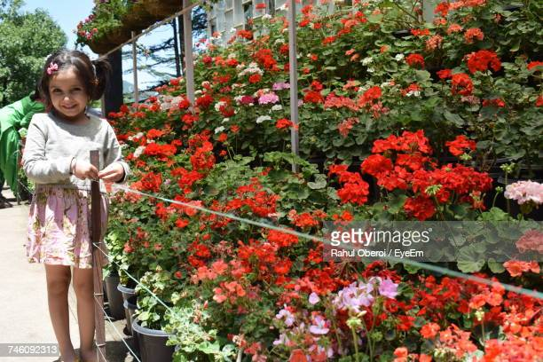 Portrait Of Smiling Girl Standing By Flower Shop