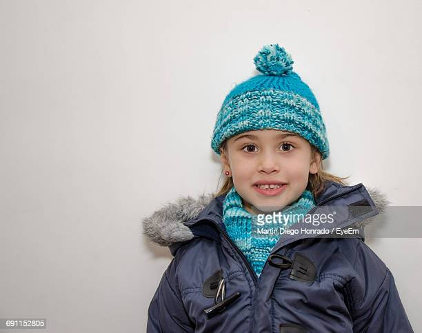 Portrait Of Smiling Girl Wearing Warm Clothing Against White Background
