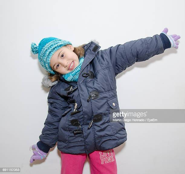 Portrait Of Smiling Girl Wearing Warm Clothing With Arms Outstretched Against White Background