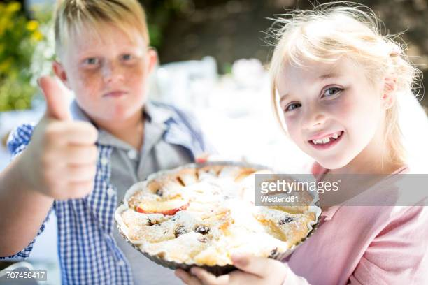 Portrait of smiling girl with brother holding a pie outdoors