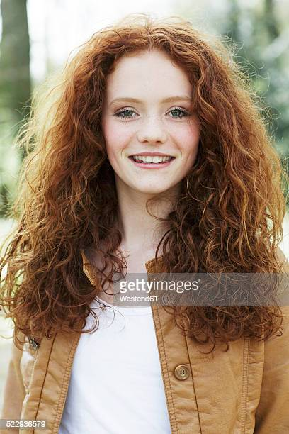 Portrait of smiling girl with curly red hair