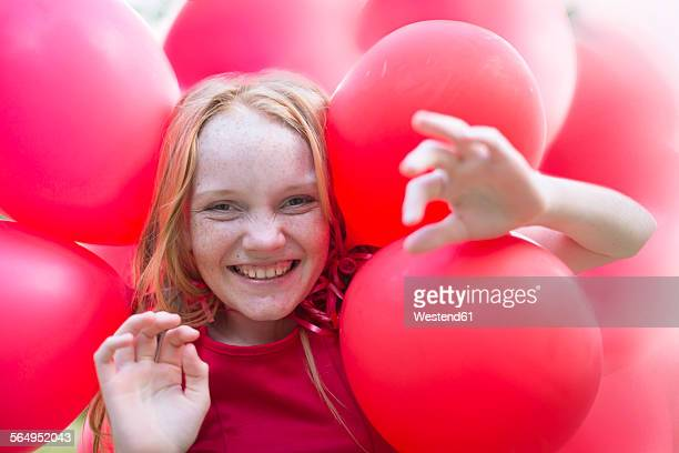 Portrait of smiling girl with red balloons