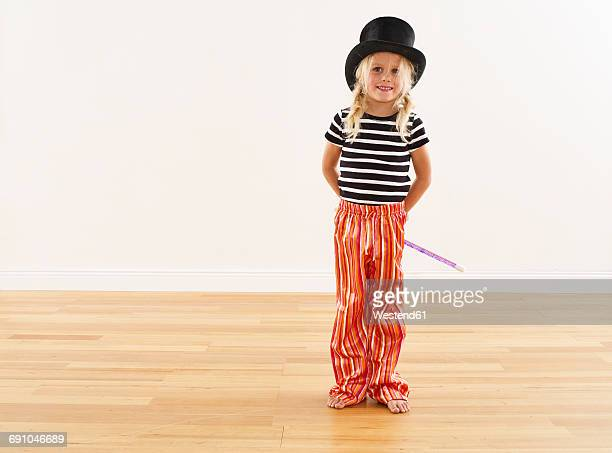 Portrait of smiling girl with top hat and magic wand