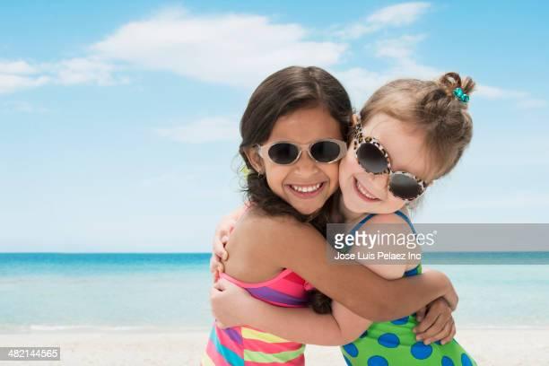 Portrait of smiling girls hugging on beach