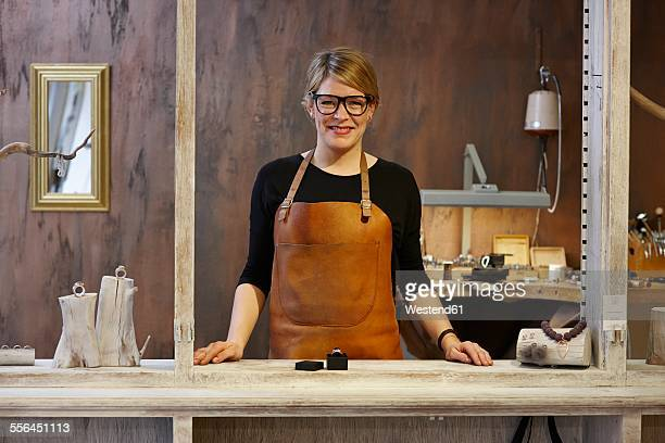 Portrait of smiling goldsmith in her shop