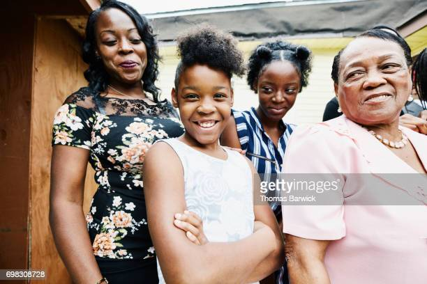 Portrait of smiling granddaughters standing with mother and grandmother