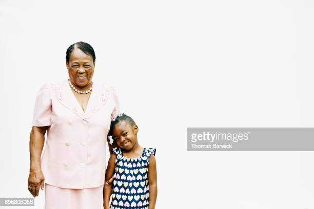 Portrait of smiling grandmother and granddaughter embracing in front of white background