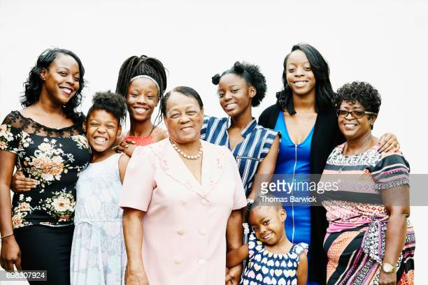 Portrait of smiling grandmother standing with daughters and granddaughters against white background