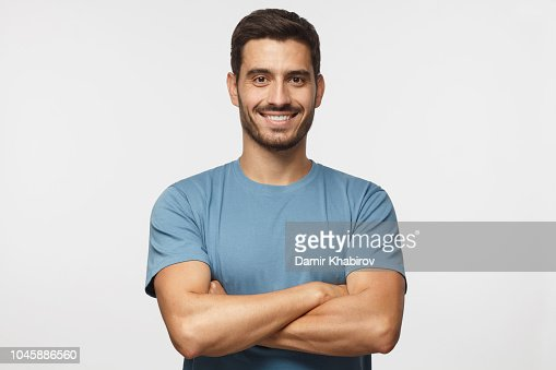 Portrait of smiling handsome man in blue t-shirt standing with crossed arms isolated on grey background : Foto de stock