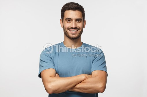 Portrait of smiling handsome man in blue t-shirt standing with crossed arms isolated on grey background : Stock Photo