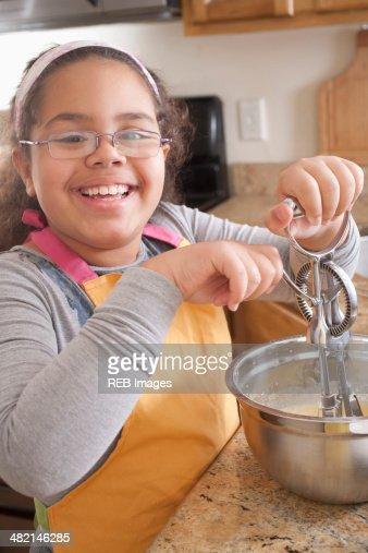 Portrait of smiling Hispanic girl baking in kitchen