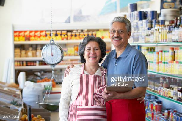 Portrait of smiling Hispanic grocery store owners