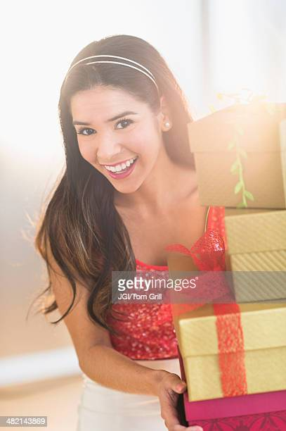 Portrait of smiling Hispanic woman carrying Christmas gifts