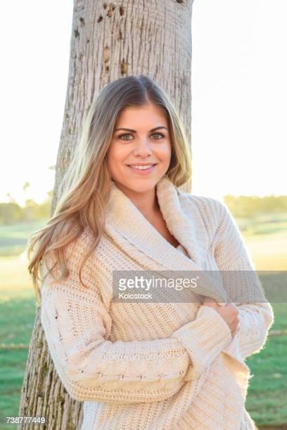 Portrait of smiling Hispanic woman leaning on tree