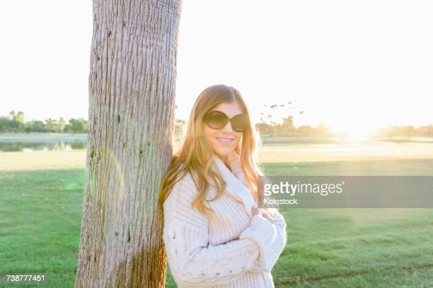 Portrait of smiling Hispanic woman wearing sunglasses leaning on tree