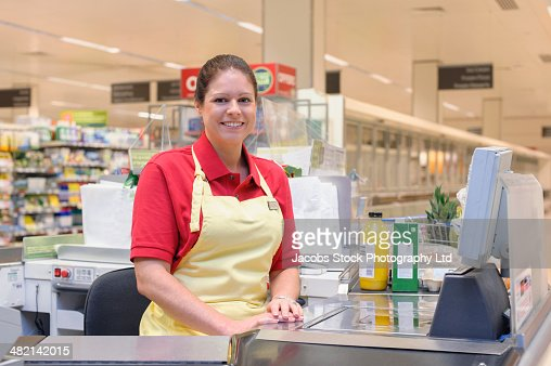 Portrait of smiling Hispanic woman working at grocery checkout