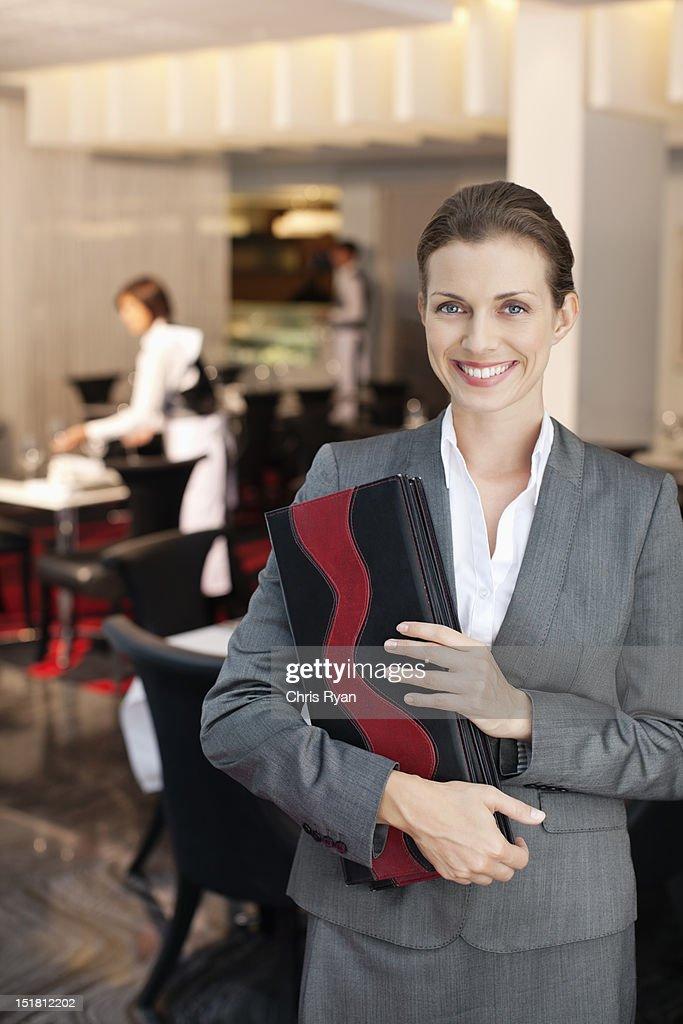 Portrait of smiling hostess in restaurant : Stock Photo