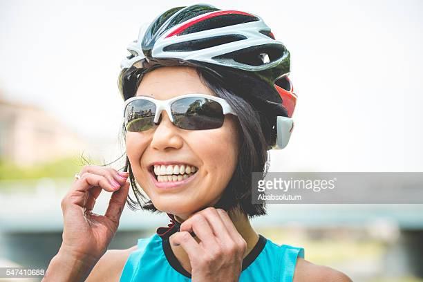 Portrait of Smiling Japanese Woman Fastening Helmet in Kyoto, Japan