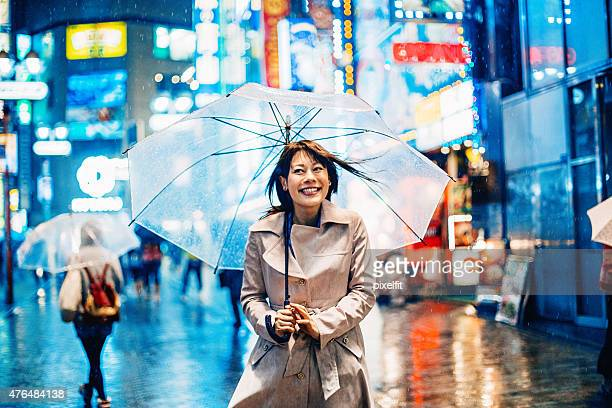 Portrait of smiling japanese woman walking in the rain