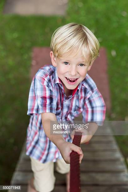 Portrait of smiling little boy climbing on a playground