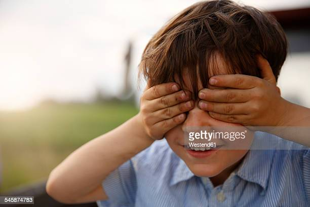 Portrait of smiling little boy covering eyes with his hands