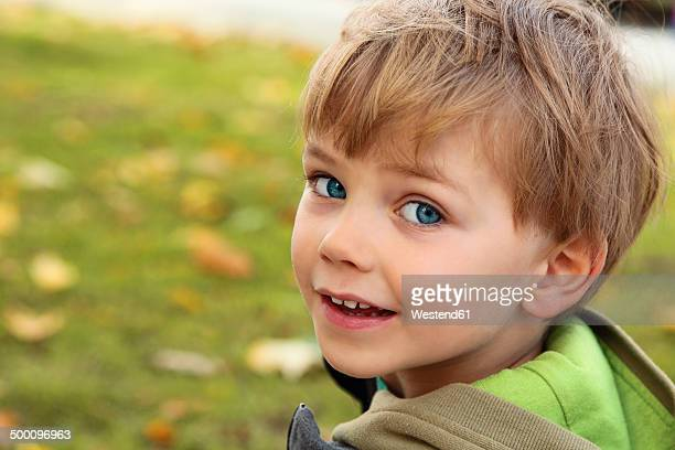 Portrait of smiling little boy looking over his shoulder