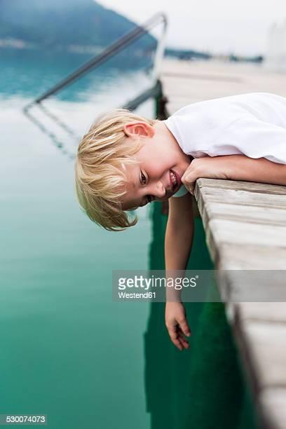 Portrait of smiling little boy lying on a jetty