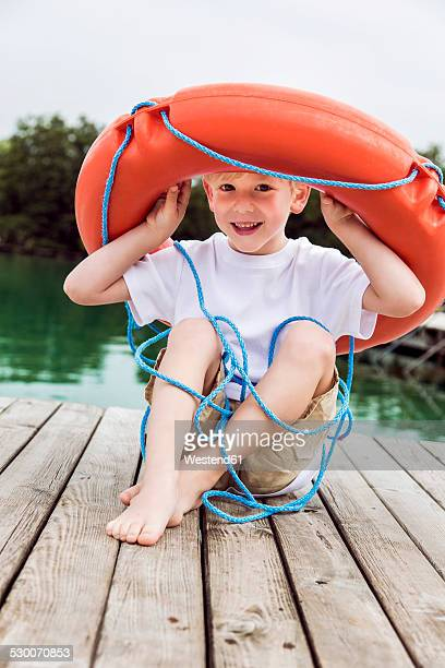 Portrait of smiling little boy sitting on a jetty playing with a lifesaver