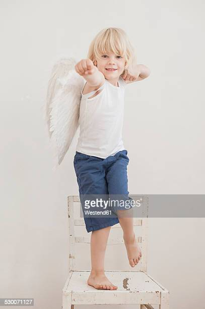 Portrait of smiling little boy with angle wings standing on a chair
