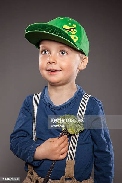 Portrait of smiling little boy with baseball cap holding broccoli