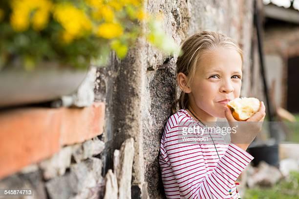 Portrait of smiling little girl eating an apple