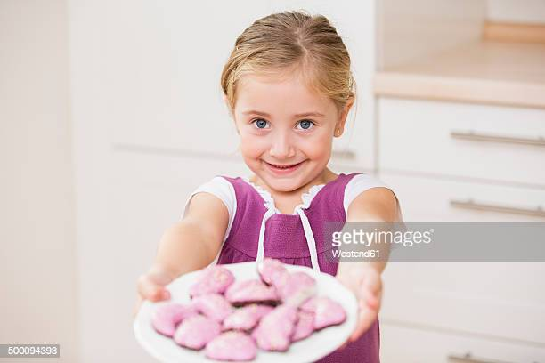 Portrait of smiling little girl holding plate of pink cookies