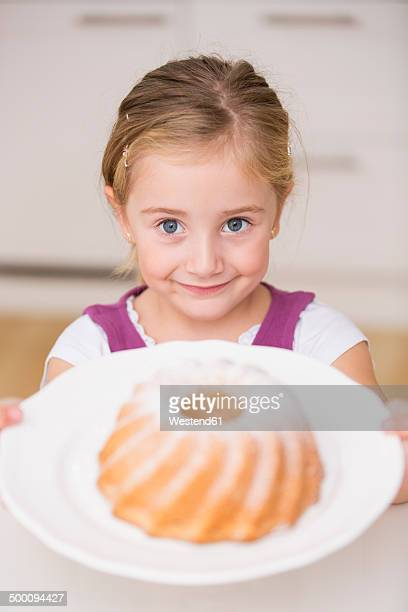 Portrait of smiling little girl holding plate with ring cake