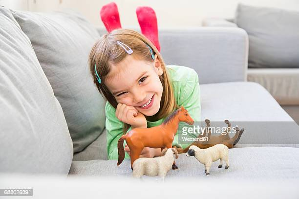 Portrait of smiling little girl lying on couch with her animal figurines