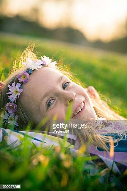 Portrait of smiling little girl lying on meadow wearing flowers