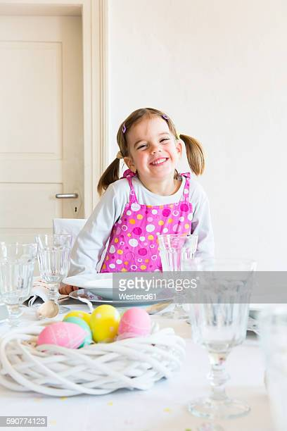 Portrait of smiling little girl sitting at laid table
