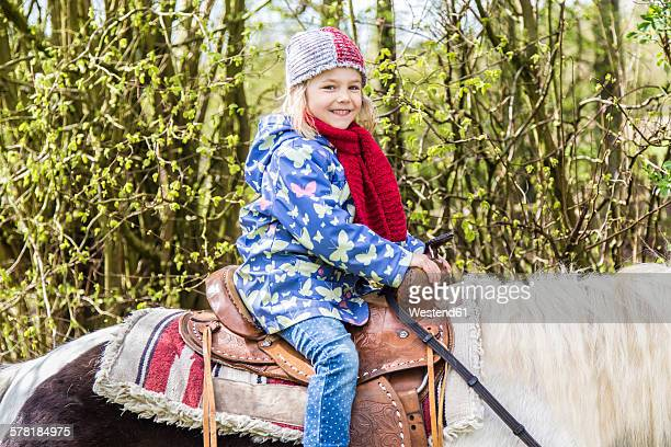 Portrait of smiling little girl sitting on a pony
