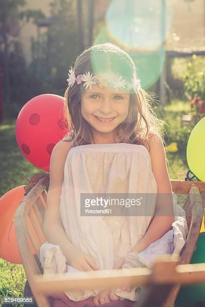 Portrait of smiling little girl wearing flowers sitting on a handcart in the garden