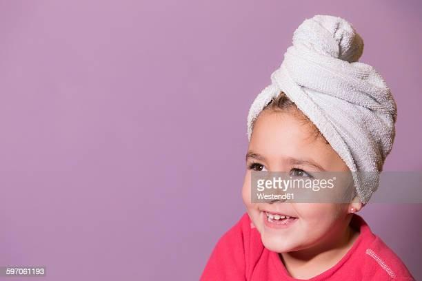 Portrait of smiling little girl wearing towel turban