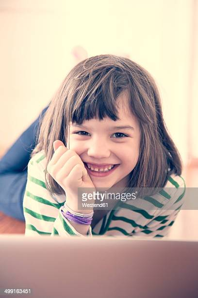 Portrait of smiling little girl with laptop at home