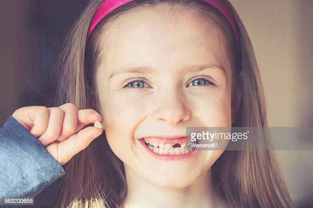 Portrait of smiling little girl with tooth gap holding milk tooth in her hand